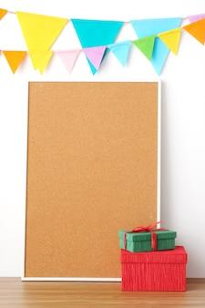 Bunte parteiflaggen, die an leerem korkenbrett und an geschenkbox auf holztischhintergrund hängen