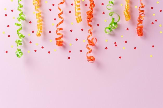 Bunte party luftschlangen auf rosa hintergrund.