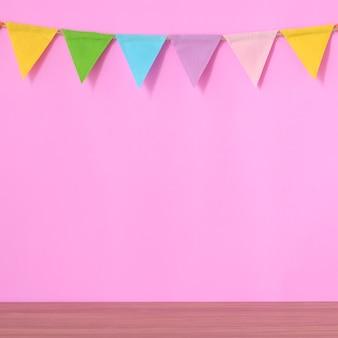 Bunte partyflaggen auf rosa hintergrund- und holztabelle
