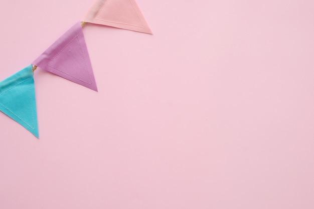 Bunte partyflaggen auf rosa hintergrund