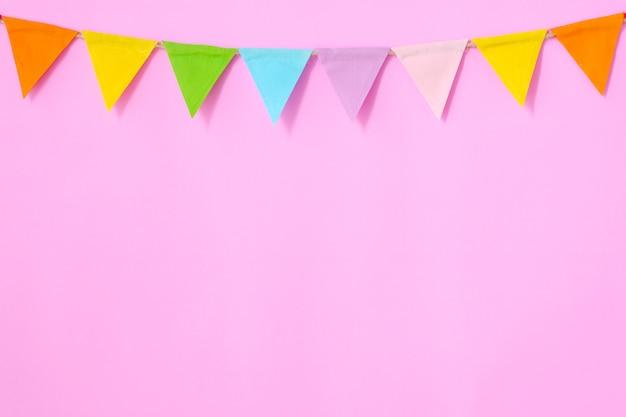 Bunte partyflaggen, die am rosa hintergrund hängen