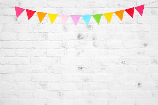 Bunte partyflaggen, die am weißen backsteinmauerhintergrund hängen