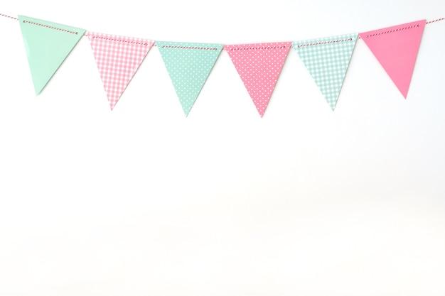 Bunte partyflaggen, die am weißen wandhintergrund, geburtstag, jahrestagskarte backgro hängen