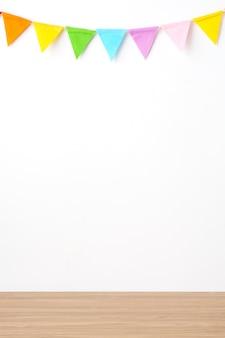 Bunte partyflaggen, die am weißen wandhintergrund und am holztischhintergrund hängen