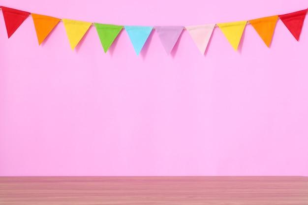 Bunte partyflaggen, die an der rosa hintergrund- und holztabelle hängen