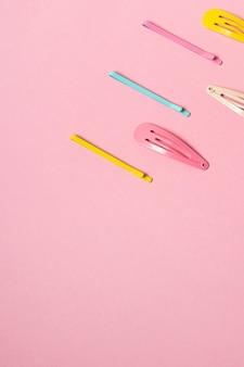 Bunte pastell-accessoires-haarnadel auf rosa hintergrund hautnah trendige moderne aus der vergangenheit