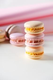 Bunte pastellfarbene französische makronen oder macarons auf weißem und rosa hintergrund