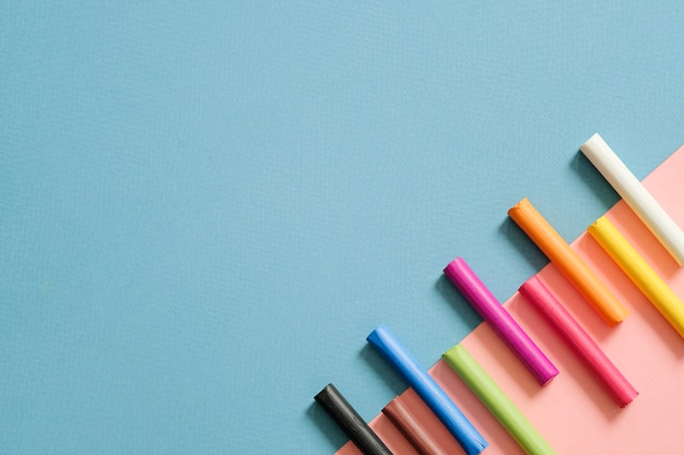 Bunte pastellstifte auf blauem und rosa geometrischem hintergrund mit kopienraum. kunst, zeichenkonzept