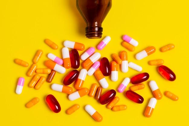 Bunte pillen auf gelbem hintergrund