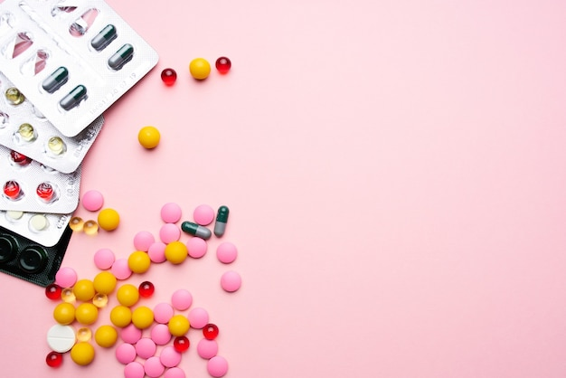 Bunte pillen, die vitamine gesundheitswesen rosa hintergrund verpacken
