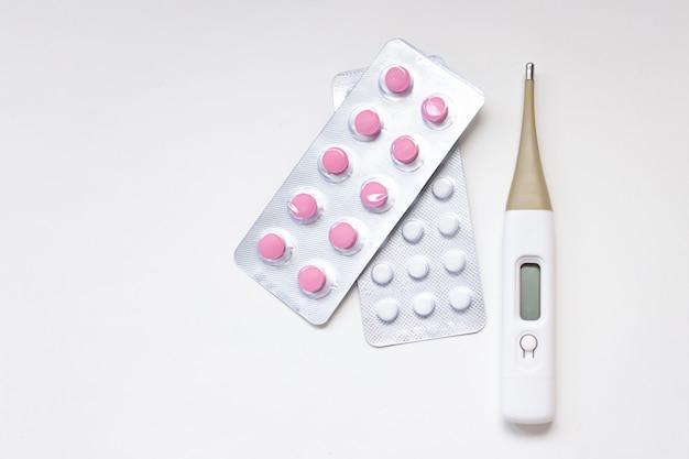 Bunte pillen, kapseln, tabletten und thermometer.