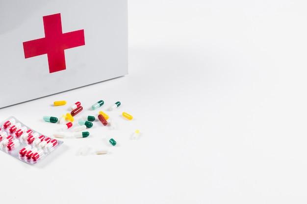 Bunte pillen mit der ausrüstung der ersten hilfe lokalisiert auf weißem hintergrund