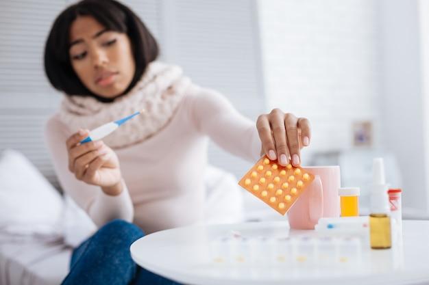 Bunte pillen. ruhige, vorsichtige, kranke frau, die ein helles päckchen mit gelben pillen von ihrem tisch nimmt