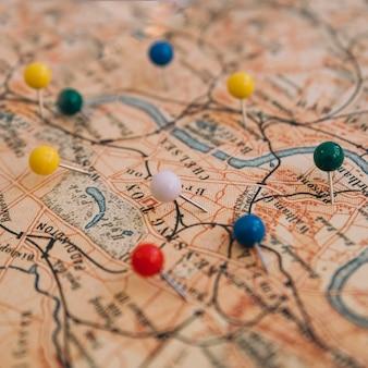 Bunte pins der nahaufnahme auf karten