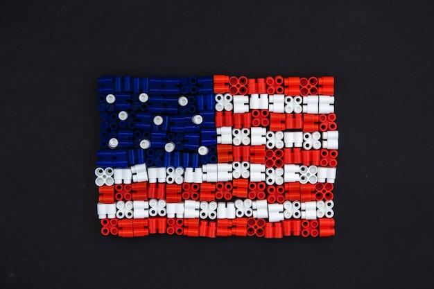 Bunte plastikbausteine, die die us-flagge auf schwarzem papierhintergrund bilden