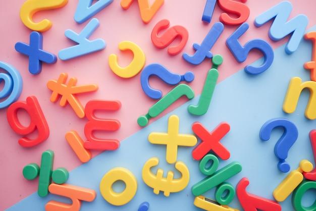Bunte plastikbuchstaben auf draufsicht des farbigen hintergrundes