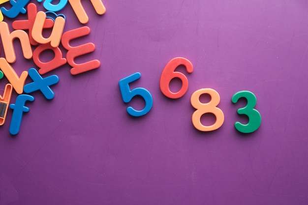 Bunte plastikbuchstaben auf lila hintergrund, draufsicht