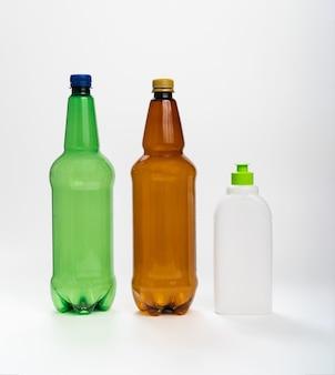 Bunte plastikflaschen auf weißem hintergrund. konzept des recyclings von kunststoff. flüssigkeitsbehälter