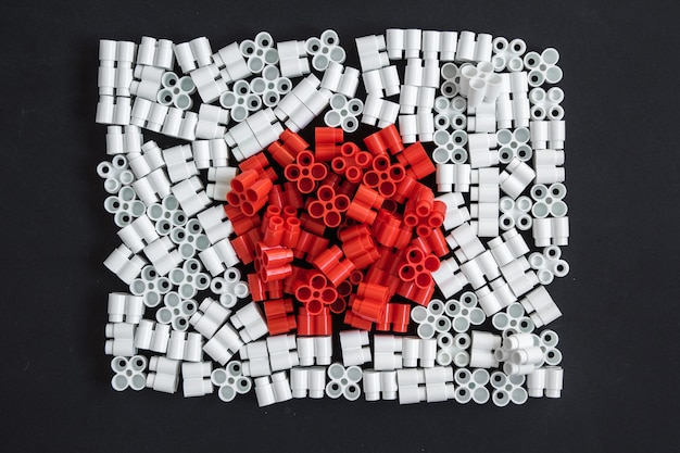 Bunte plastiksteine, die die flagge japans auf dem hintergrund von schwarzem papier bilden