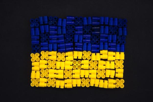 Bunte plastiksteine, die die ukraine-flagge auf schwarzem papierhintergrund bilden
