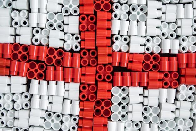 Bunte plastiksteine, die im hintergrund die flagge englands bilden