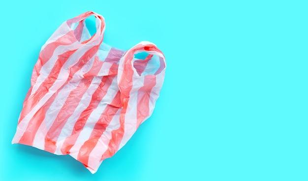 Bunte plastiktüte auf blauem hintergrund. speicherplatz kopieren