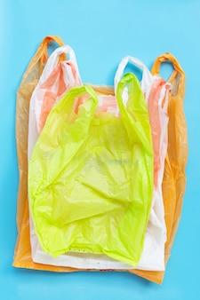 Bunte plastiktüten auf blauem hintergrund. umweltverschmutzungskonzept