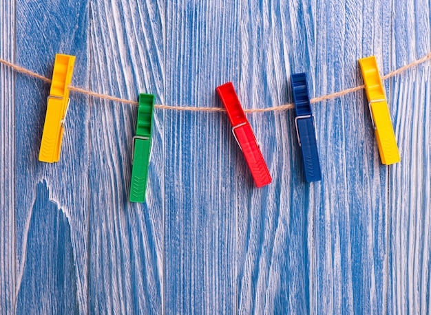 Bunte plastikwäscheklammern auf blauem hölzernem hintergrund