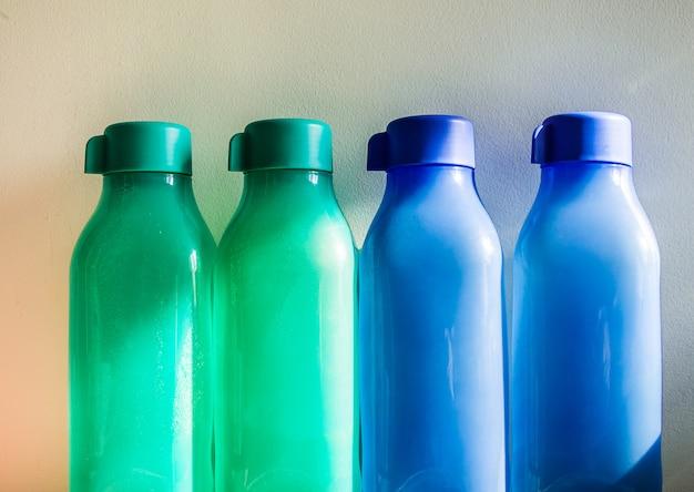 Bunte plastikwasserflaschen auf der weißen wand