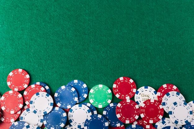Bunte pokerchips auf grünem hintergrund