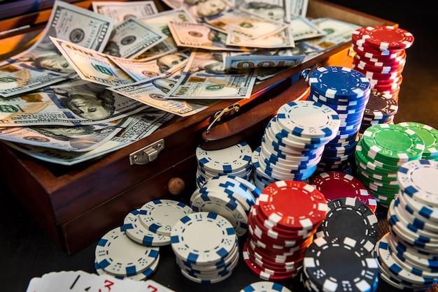Bunte pokerchips mit spielkarten und us-dollar auf dunklem hintergrund.