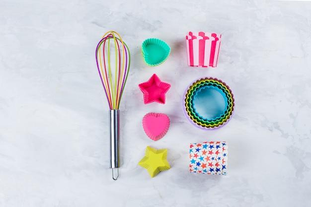 Bunte regenbogen-küchengeräte für bäckerei auf weißem marmortabellenhintergrund. draufsicht