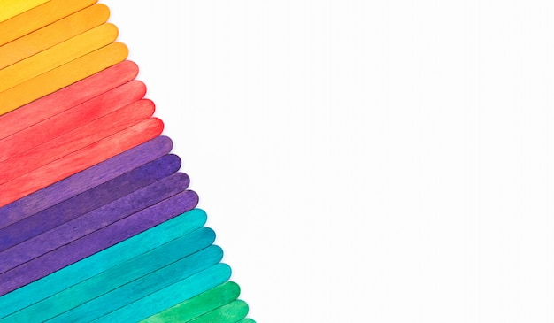 Bunte regenbogenholz-eis am stiel auf weißem papier mit kopierraum, abstrakte farbstifte decken rahmen für kinderkunsthandwerksarbeiten ab, kinder zurück zum schulkonzept