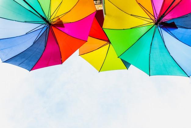 Bunte regenschirme als hintergrund für helle und fröhliche ideen.