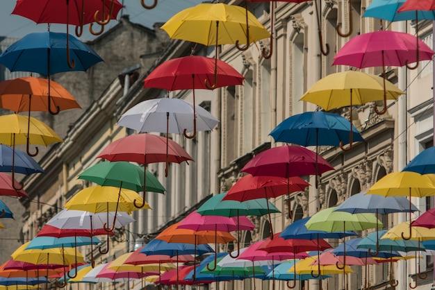 Bunte regenschirme hängen am hintergrund der alten stadt im lemberg