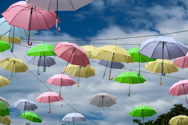 Bunte regenschirmlinie draht, der durch wind auf blauem himmel sich bewegt