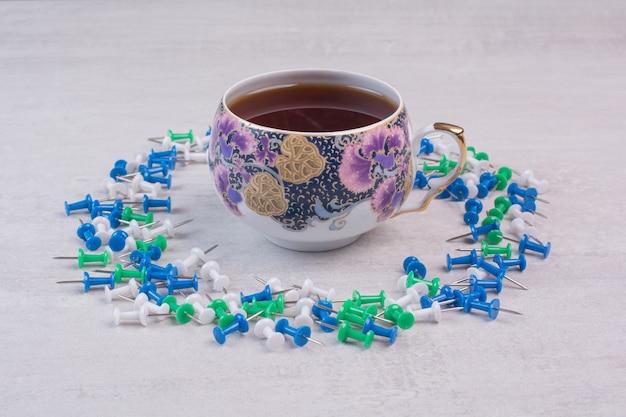 Bunte reißnägel und eine tasse tee auf weißer oberfläche