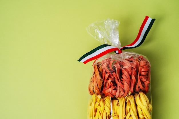 Bunte rohe italienische teigwaren in der transparenten plastiktasche auf grünem hintergrund. hausgemachte farbige pasta.