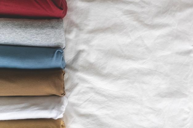 Bunte rollen des t-shirts auf dem weißen bett