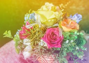 Bunte Rosen mit grünem Blatt im Vasengoldlicht, Weinleseart.