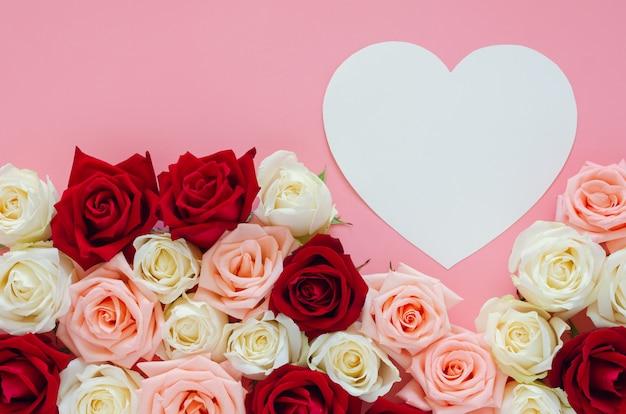 Bunte rosen und papierherz auf rosa
