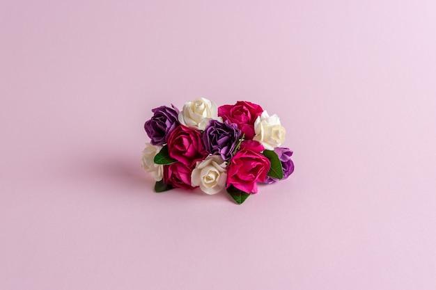 Bunte rosenblumendekoration auf pastellrosa hintergrund