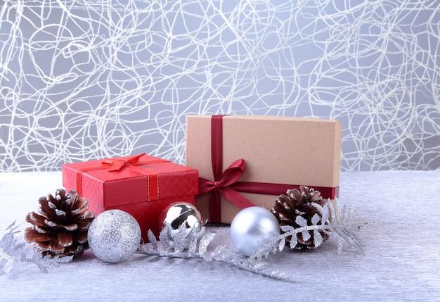 Bunte rote geschenke mit den weihnachtsbällen lokalisiert auf silber