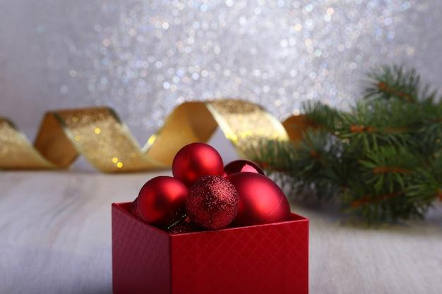 Bunte rote geschenke mit den weihnachtsbällen lokalisiert auf silbernem hintergrund
