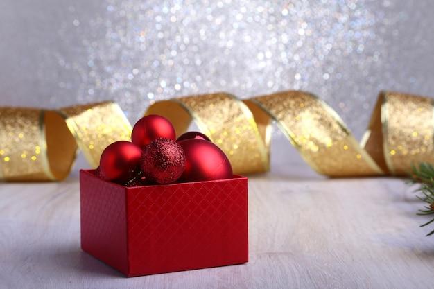Bunte rote geschenke mit den weihnachtsbällen lokalisiert auf silberner oberfläche