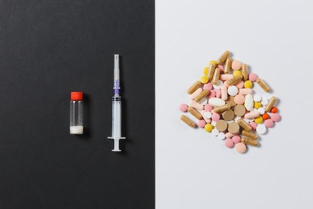 Bunte runde tabletten der medikamente, kapsel, pillen, die abstrakt auf weißem schwarzem hintergrund angeordnet sind