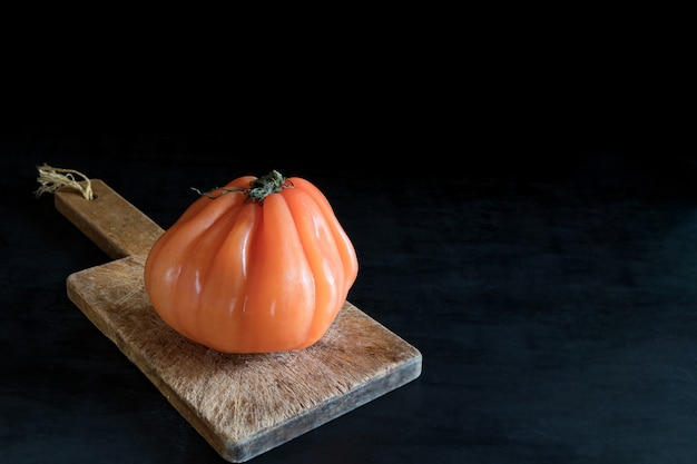 Bunte saftige hässliche tomate auf hölzernem schneidebrett auf einer schwarzen tabelle, einer rustikalen art und einem zurückhaltenden