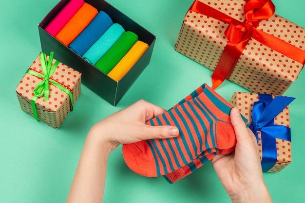 Bunte sammlung von baumwollsocken als geschenk in frauenhänden.