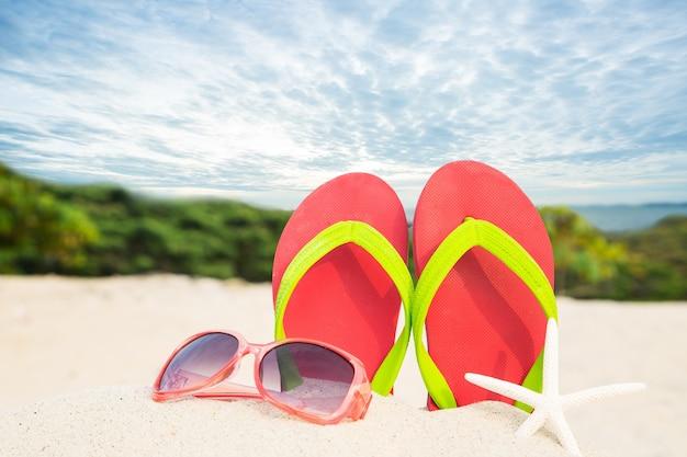Bunte sandalen am strand mit sommerkonzept.