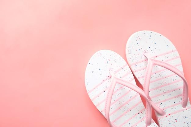 Bunte sandalen auf rosa hintergrund von oben nach unten.